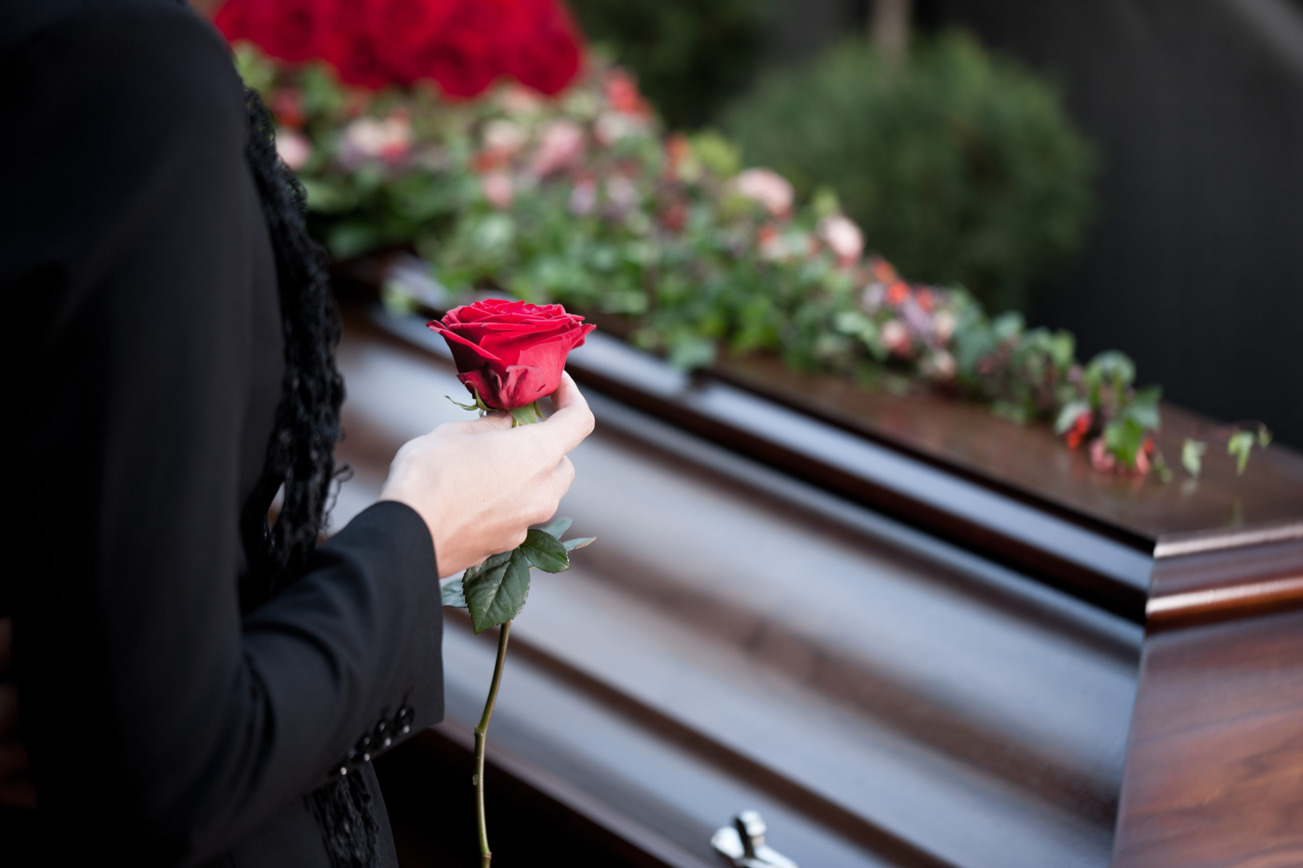 Woman holding rose next to casket